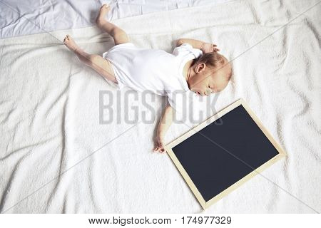 newborn baby with a greeting card lying on the sofa, on white background