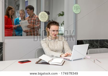 Cute female Freelancer in casual white Sweater working on Laptop Computer at grey Desk inside Open Space Office vintage Notepad and red Telephone on Table other People discussing on background.