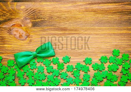 St Patrick Day background - green quatrefoils and bow tie on the wooden background. St Patrick Day background with free space for text. Concept of St Patrick Day holiday. St Patrick Day is national Irish holiday