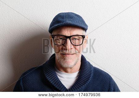 Handsome senior man in blue sweater, flat cap and black eyeglasses. Studio shot against white wall.