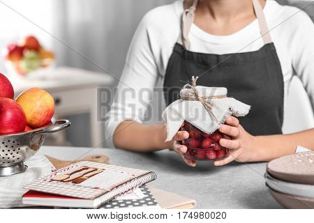Woman in apron holding jar with jam and sitting at kitchen table