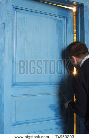 Young man peeking in the door slot. Obscure witness.