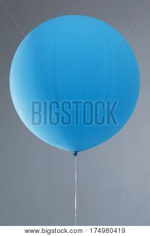 one blue inflated balloon on white background