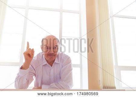 Boss reprimands at work. An elderly man in a white shirt and tie shows the index finger up against the window.