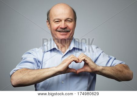 old man making out of hands heart. Doing charity work take care of the health or being in love