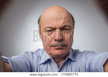 Aged Man Dissatisfied Frowns And Looks Sullenly. Wrinkles On The Forehead Of Negative Events