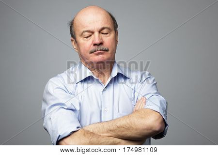 Elderly Man Falls Asleep On Standing With His Arms Crossed On His Chest. Drowsiness From Fatigue At