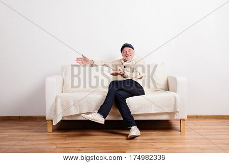 Handsome senior man in beige sweater smiling, sitting on sofa, legs crossed. Studio shot against white wall.