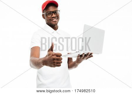 Photo of cheerful young african man wearing cap isolated over white background using laptop computer make thumbs up gesture. Looking at camera.