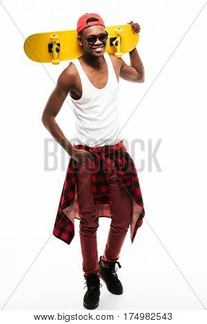 Full length of cheerful african young man standing and holding skateboard on his shoulder over white background