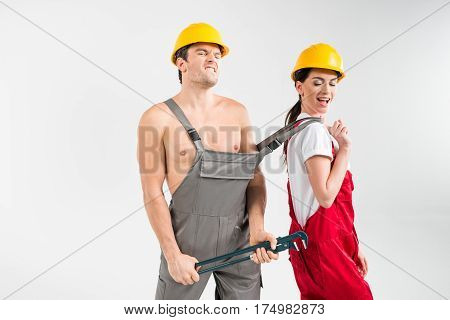Young male and female builders in helmets posing on grey