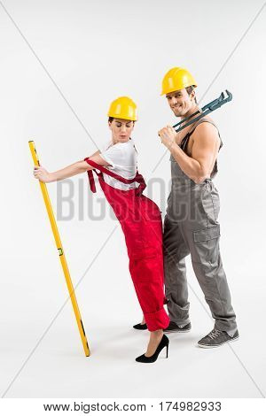 Young male and female builders posing with tools on grey