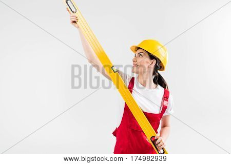 Smiling female engineer in helmet holding level tool on grey