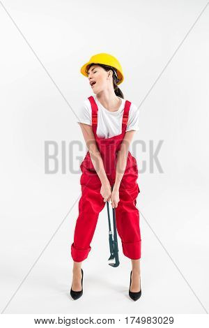Female builder in high-heeled shoes posing with pipe wrench on grey