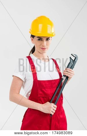 Attractive female builder in helmet holding pipe wrench on grey