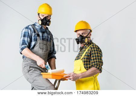 Two workmen in protective workwear with paint roller and paint