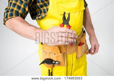 Mid section of workman with tool belt on grey