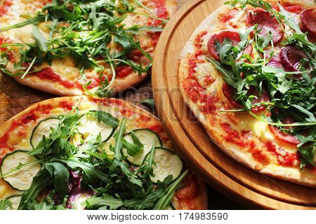Different variations of pizza.Pizza with sausage, zucchini, olives, cheese rucola. Top view.