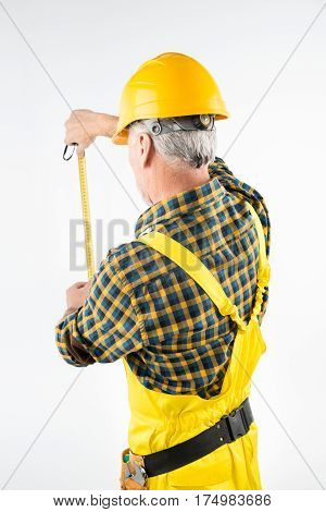 Mature workman in hard hat working with flexible ruler