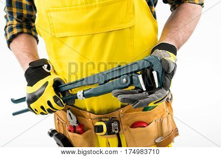 Mid section of workman with tool belt holding pipe wrench