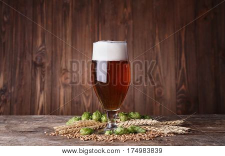 Glass of dark beer and its ingredients on table against blurred wooden background