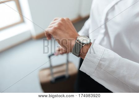 Close up portrait of business woman checking time on her watch and holding suitcase