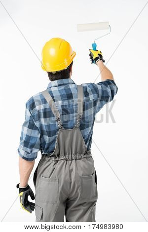 Back view of workman painting wall with paint roller