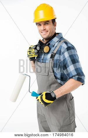 Smiling workman in protective workwear holding paint roller