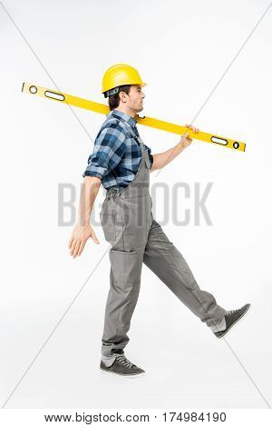 Side view of workman with level tool walking on white