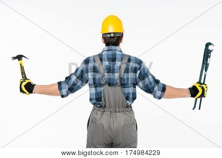 Back view of workman holding hammer and pipe wrench on white
