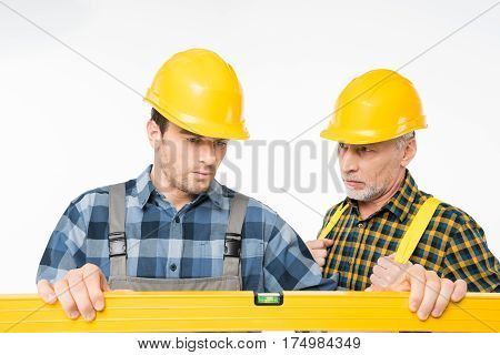 Two serious workmen working with level tool on white