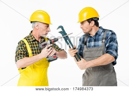 Two male construction workers fighting with tools and looking at each other