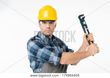 Professional male construction worker in helmet and protective eyewear holding pipe wrench