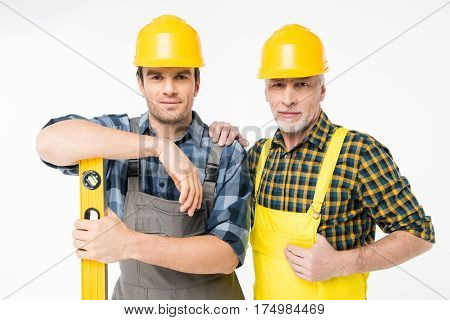 Two workmen in helmets standing with level tool and smiling at camera