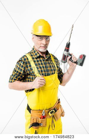 Smiling mature workman in protective workwear holding electric drill