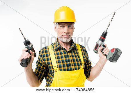 Smiling mature workman in protective workwear holding electric drills