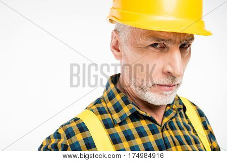 Close-up portrait of mature workman in hard hat looking at camera
