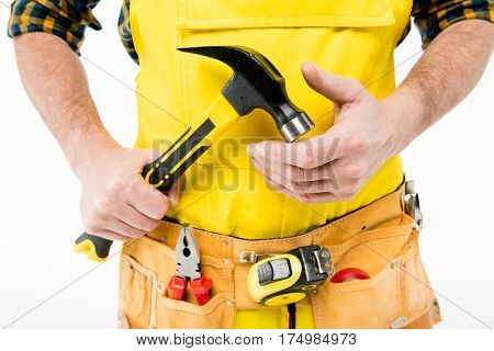 Partial view of workman in tool belt holding hammer on white