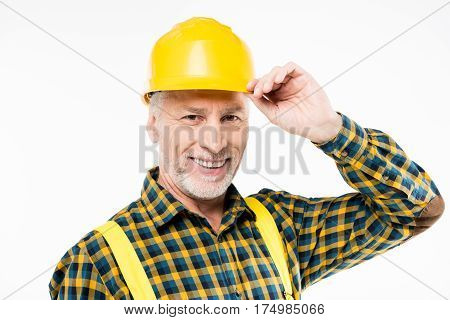 Portrait of mature workman in hard hat smiling and looking at camera