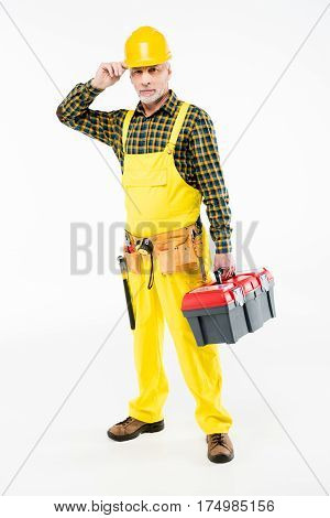 Mature workman in hard hat holding tool kit and looking at camera on white