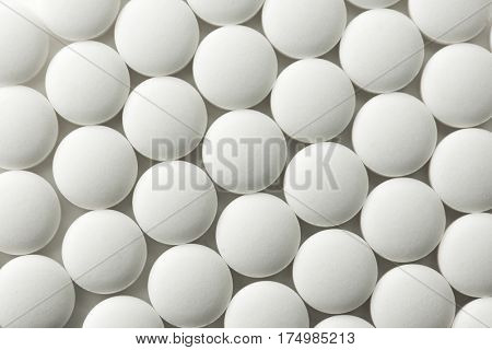 White pills or pharmaceutical tablets, shot from above.