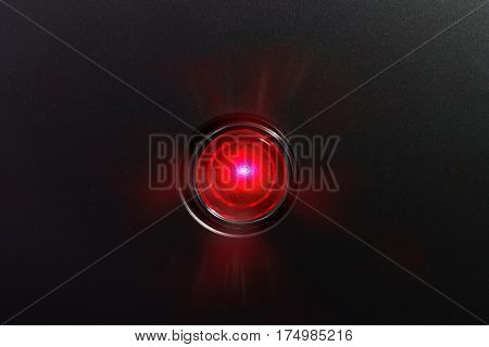 Red glowing status indicator, warning lamp or button, on black panel.