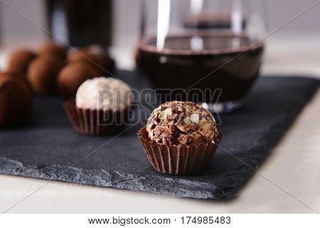 Delicious chocolate truffles and red wine closeup