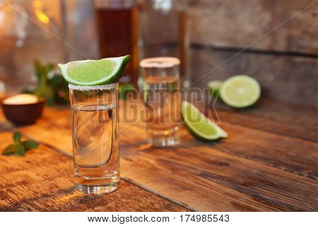 Tequila shots with juicy lime and salt on wooden table
