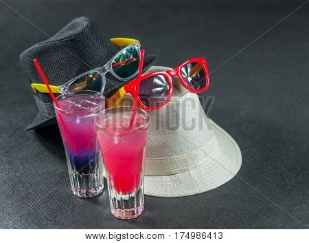 Two colored drinks a combination of dark blue with purple the second combination of red with pink long drink glass yellow and red sunglasses white and black hats party set