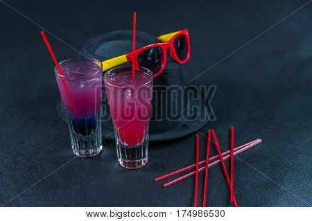 Two colored drinks a combination of dark blue with purple the second combination of red with pink long drink glass yellow and red sunglasses black hat party set
