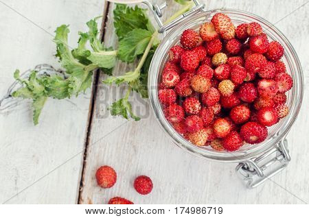 Wild strawberry in glass jar with green mint leaves on white rustic wooden background. Sweet berry Fragaria for summer dessert. Healthy snack. Top view.