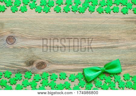 St Patrick's Day. St Patricks Day background - green quatrefoils and bow tie on the wooden background. St Patrick's Day concept with St Patrick's Day symbols. St Patrick's Day background