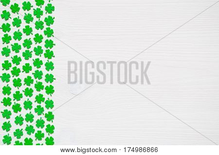 St Patricks Day background - border of green quatrefoils on the white wooden surface. St Patricks Day background with clover bordes. St Patricks Day concept. St Patricks Day background with free space for text