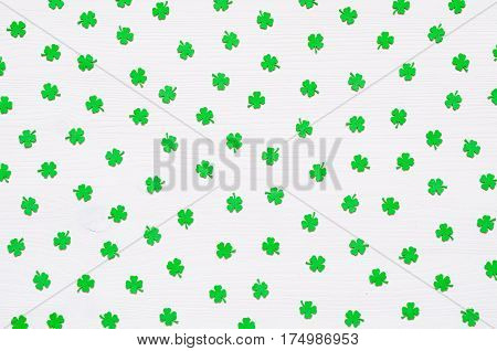 St Patricks Day holiday background - green quatrefoils on the white wooden surface. St Patrick's Day festive background. St Patrick's Day conceptual background. St Patrick's Day background